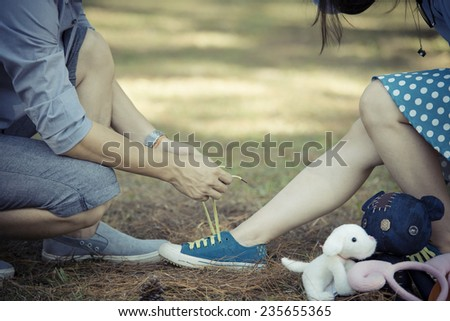 man tying a shoelaces on the woman shoes - stock photo