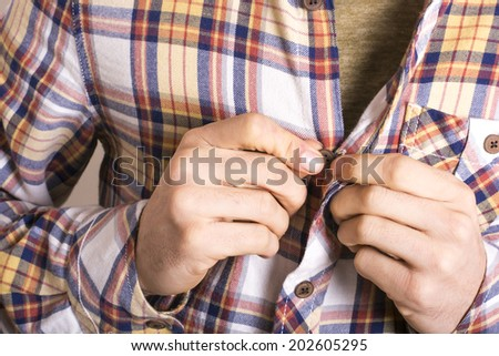 Man tying his shirt on a white background - stock photo