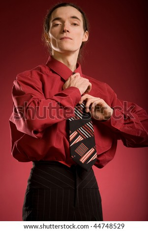 Man tying his tie on red background - stock photo