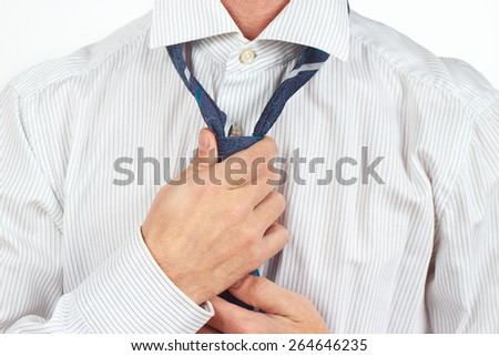 Man tying his tie over bright shirt close up - stock photo