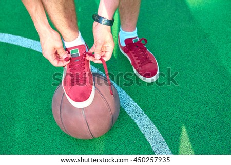Man tying shoelaces relying on basketball ball