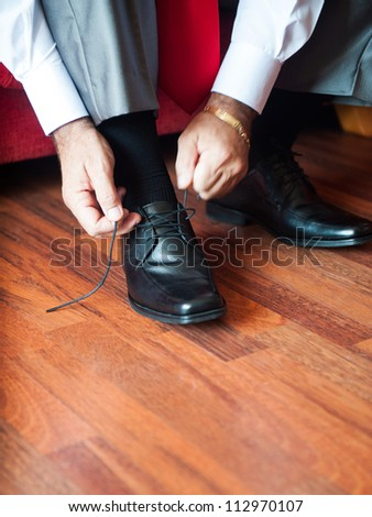 Man tying the laces on black shoes on a wooden floor