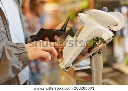 Man typing his PIN password at supermarket checkout in card reader - stock photo