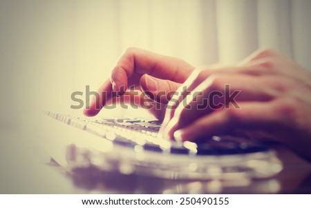 man typing on a keyboard with a retro instagram filter (shallow depth of field) - stock photo
