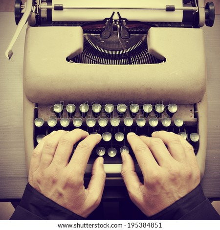 man typing on an old typewriter, with a retro effect - stock photo