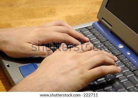 Man typing on laptop computer. - stock photo