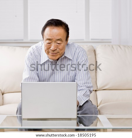 Man typing on laptop in livingroom