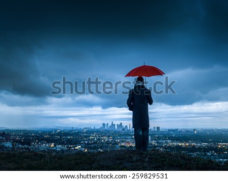 Man under red umbrella overlooking stormy Los Angeles cityscape from Hollywood Hills at twilight.  - stock photo