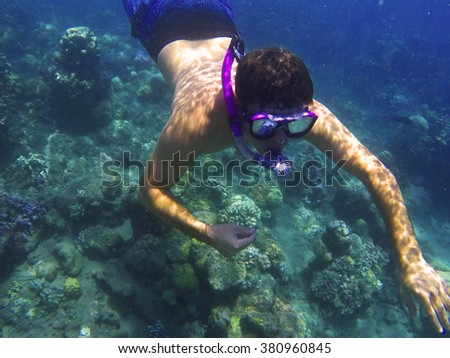 Man underwater in mask, snorkeling in blue sea, diving to coral reef, tropical sea snorkeling, summer vacation sport activity, snorkeling man on summer holiday, caucasian man in mask snorkeling in sea - stock photo