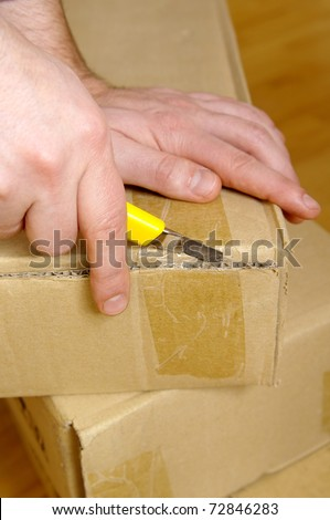 Man unpacking box with cutter - stock photo