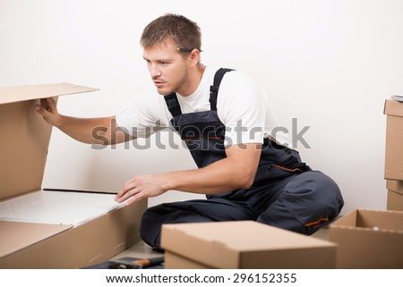Man unpacking things after relocating to new home. DIY, new home and moving concept - stock photo