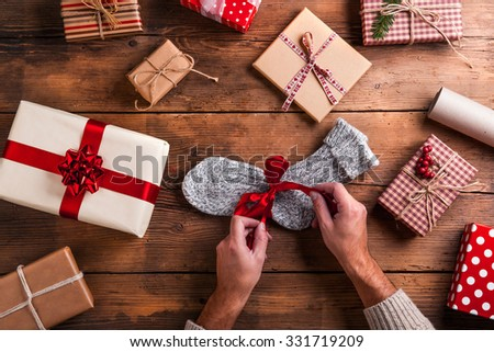 Man unwrapping Christmas present laid on a wooden table background - stock photo