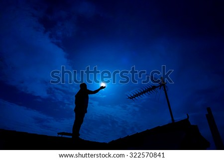 Man up on the roof,  holding full moon in hand against night sky - stock photo