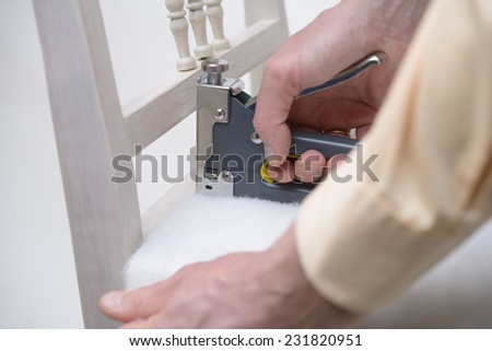 Man upholstering a chair seat using stapler - stock photo