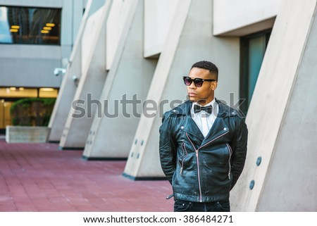 Man Urban Autumn/Spring Casual Fashion. Wearing black leather jacket, black jeans, sunglasses, white undershirt, black bow tie, a young African American guy standing on street in New York. City Boy.  - stock photo