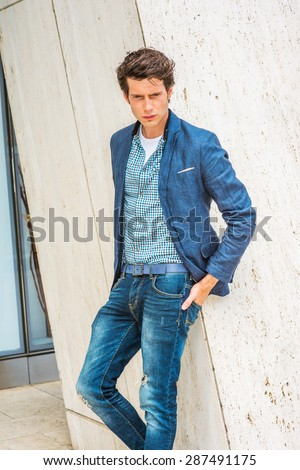 Man Urban Casual Fashion. Wearing blue blazer, patterned under shirt, jeans, hands in back pockets, a young European college student standing by column, looking down, sad, thinking, lost in thought. - stock photo