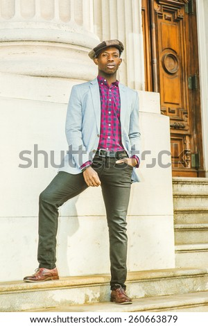 Man Urban Fashion. Wearing fashionable newsboy cap, dressing in light gray blazer, patterned pink, black under shirt, black pants, brown leather shoes, a young black guy confidently standing on stairs - stock photo