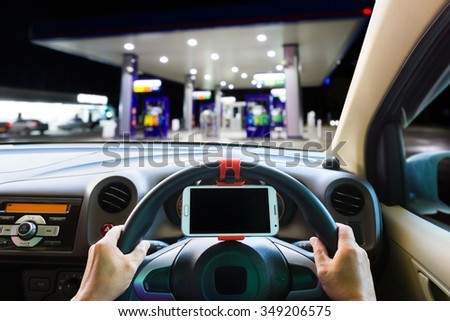 Man use mobile phone in the car at gas station. - stock photo