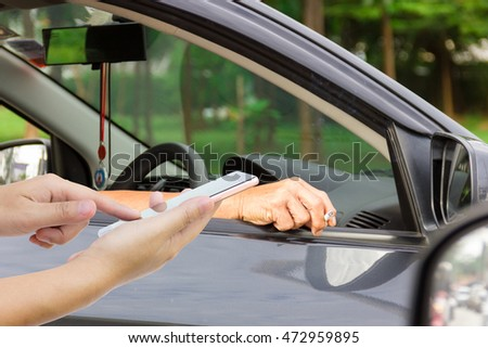 Man use mobile phone, man smoking in car as background.