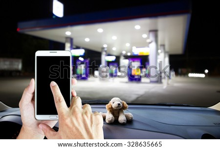Man use mobile phone on the car, blur image of gas station in the background.  - stock photo