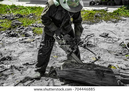 Man used electric chain saw to cutting tree trunk , destroy world concept , green splash tone.