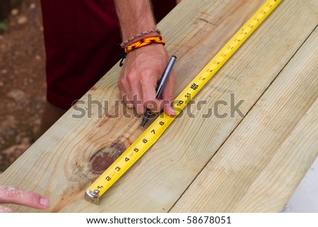 Man uses a tape measure to mark the length of a piece of lumber. - stock photo