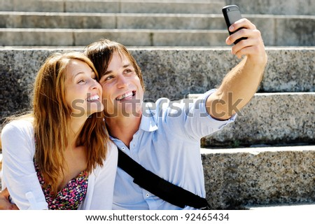 Man uses his smart phone camera to snap a picture of him and his girlfriend on honeymoon - stock photo