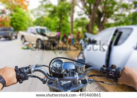 Man using a cell phone while riding a motorcycle,  blur image of accidents on the road as background.
