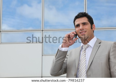 Man using a cellphone outside a mirrored building - stock photo