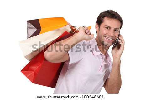 Man using a cellphone with bags of shopping - stock photo