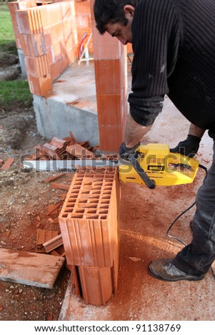 Man using a chainsaw to cut through a brick - stock photo