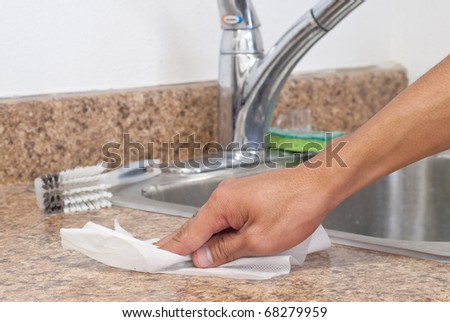 Man Using a Disinfectant Wipe on Kitchen Counter - stock photo