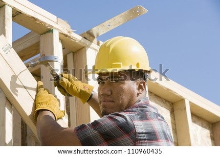 Man using a hammer to nail a wood at construction site