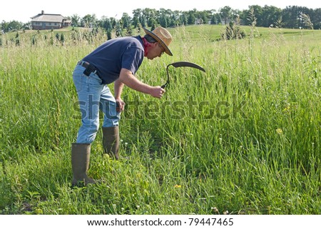 man using a hand sickle to trim weeds along a ditch - stock photo