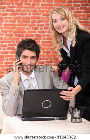 Man using a laptop and mobile phone in a restaurant - stock photo