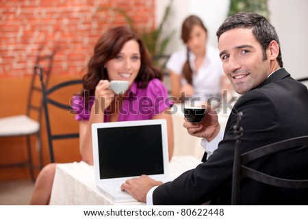 Man using a laptop computer in a cafe with a blank screen for your image