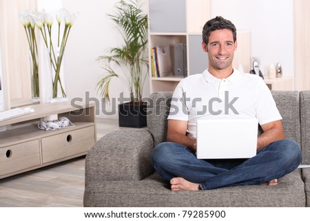 Man using a laptop computer in his front room - stock photo