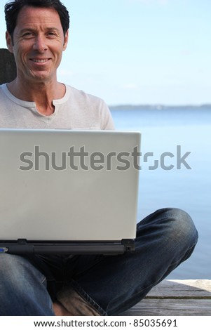 Man using a laptop computer on the waterfront