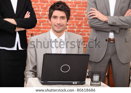Man using a laptop flanked by people in suits - stock photo