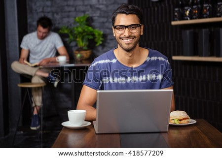Man using a laptop in a coffee shop - stock photo