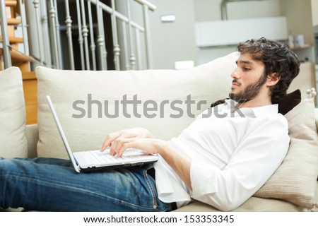 Man using a laptop while relaxing on the couch