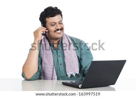 Man using a laptop while talking on a mobile phone - stock photo