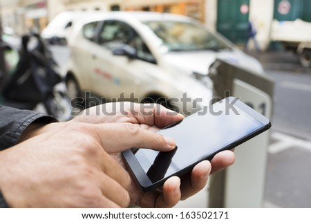 Man using a mobile phone in front of Autolib Station, Paris - stock photo