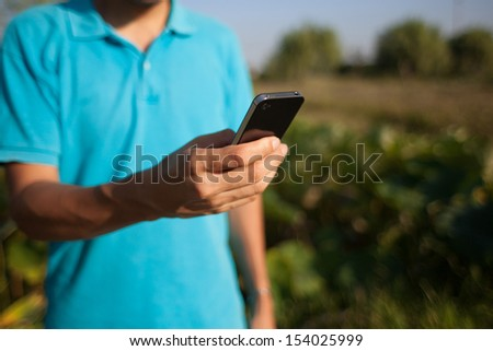 Man using a mobile smartphone in nature - stock photo