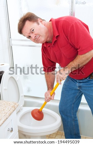 Man using a plunger to unclog a bathroom toilet.   - stock photo