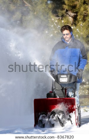 Man using a powerful snow blower in wintertime (shallow focus point on the snow blower). - stock photo