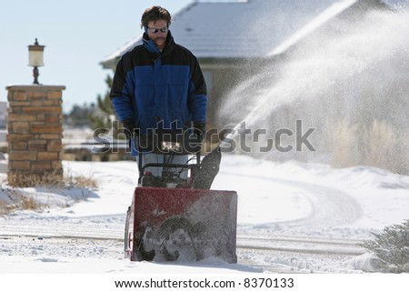 Man using a powerful snow blower in wintertime, with a large house in the background (shallow focus point on the snow blower). - stock photo