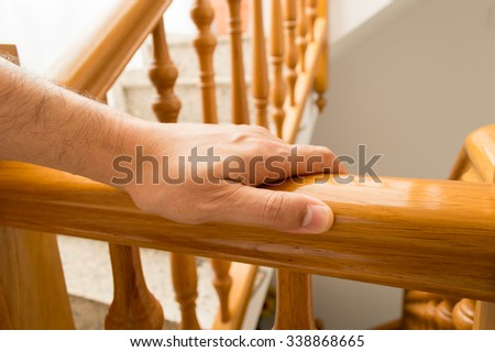 man using a railing to go downstairs at home - stock photo