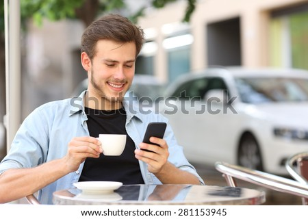 Man using a smart phone in a coffee shop sitting in the terrace outdoor and holding a cup - stock photo