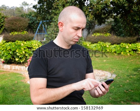 Man using a smart phone. The man is Caucasian and is outdoors. - stock photo